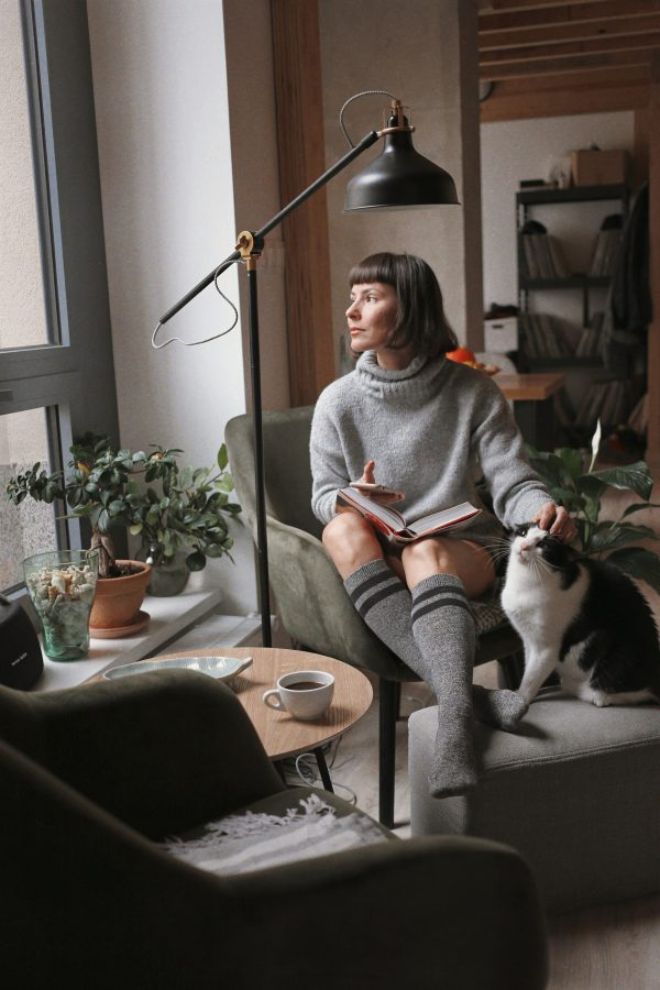 woman in gray sweater sitting on chair beside black and white cat